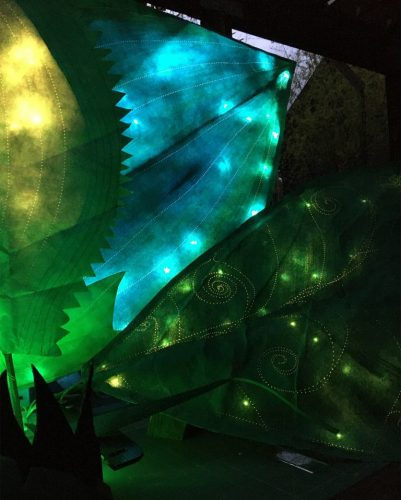 Misty Post installation of green tyvek leaves with lights